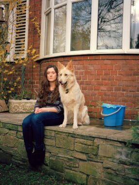 A person and a dog sitting on a stone ledge outside a house Description automatically generated with low confidence