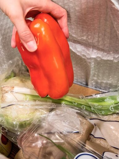 hand pulls red pepper from box of packaged ingredients